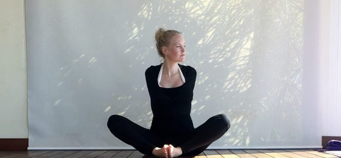 girl doing yoga interlacing fingers behind back